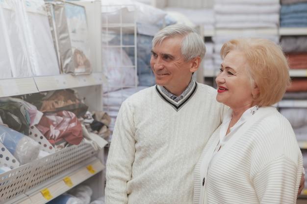 Encantadora pareja senior de compras en la tienda de muebles