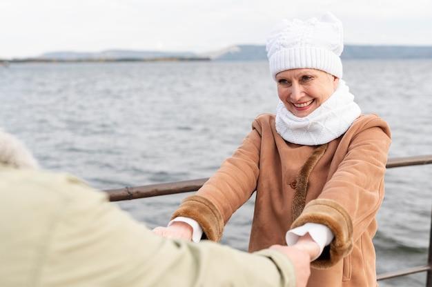 Encantadora pareja senior en spinning junto al mar