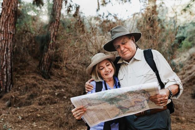 Encantadora pareja senior usando un mapa para buscar dirección