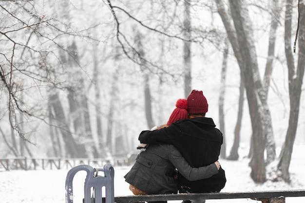 Encantadora pareja sentada en un banco y abrazando
