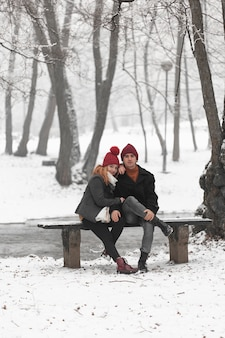 Encantadora pareja sentada en un banco vista larga