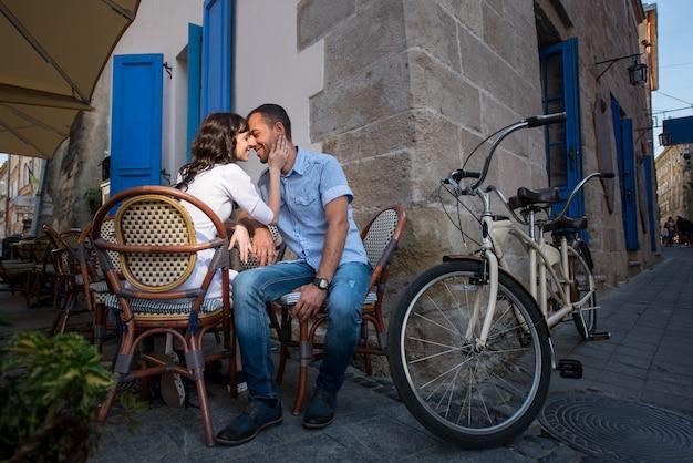 Encantadora pareja sentada en la cafetería de la acera cerca de su bicicleta tándem