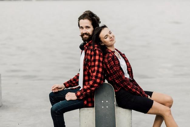 Encantadora pareja sentada espalda con espalda