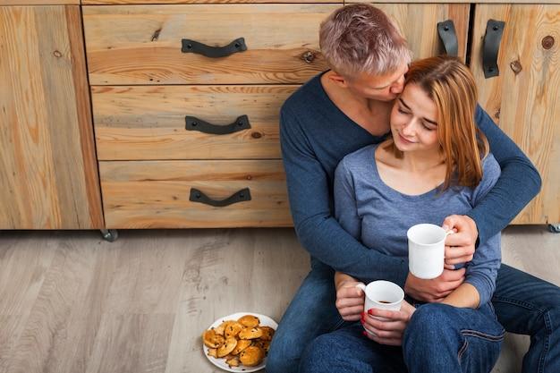 Encantadora pareja sentada en el piso de la cocina