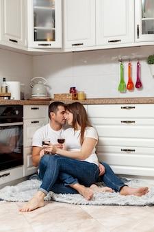 Encantadora pareja sentada en el piso y sosteniendo copas con vino