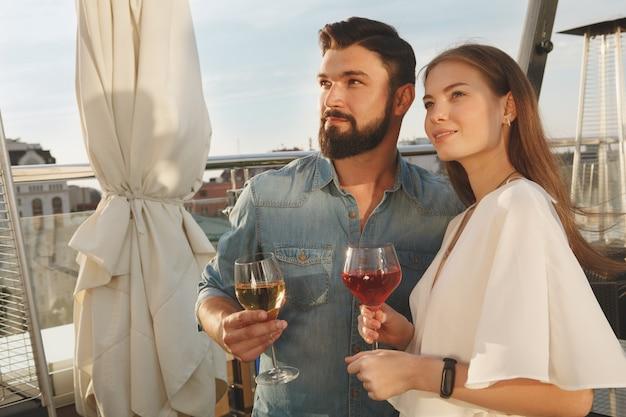 Encantadora pareja sonriendo, mirando a otro lado con alegría mientras bebe vino en la terraza del bar