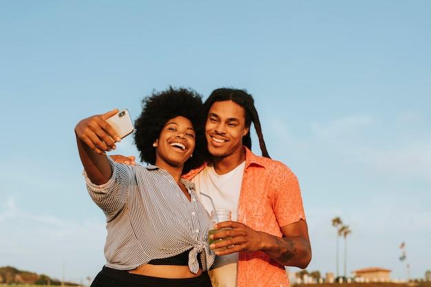 Encantadora pareja tomando un selfie en la playa