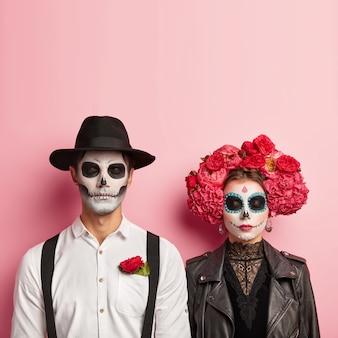 Encantadora pareja usa disfraz de zombie para halloween, tiene maquillaje de calavera, el hombre usa sombrero y camisa blanca con rosa roja en el bolsillo, mujer con chaqueta de cuero negro y corona de flores, espere la fiesta juntos