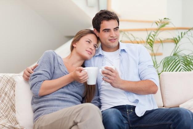 Encantadora pareja viendo la televisión mientras bebe café