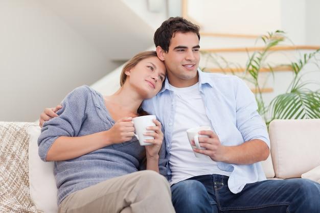 Encantadora pareja viendo la televisión mientras bebe té