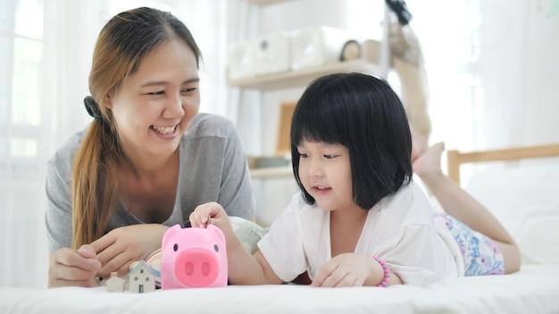 Encantadora pequeña niña asiática y madre poniendo dinero en la hucha para el ahorro