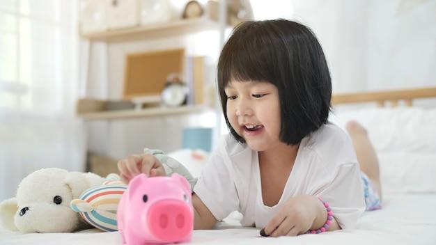 Encantadora pequeña niña asiática poniendo dinero en la hucha para el ahorro