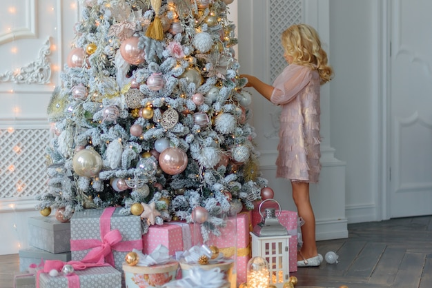 Encantadora pequeña rubia con el pelo rizado en un hermoso vestido rosa, adorna la navidad