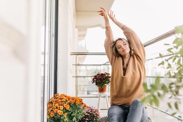 Encantadora señorita que se extiende en el balcón. retrato de interior de niña rubia satisfecha posando con las manos en alto.