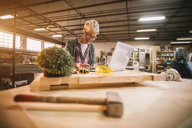 Encantadora sonrisa motivada ingeniera de cabello corto con anteojos trabajando con planos y computadora portátil en el taller