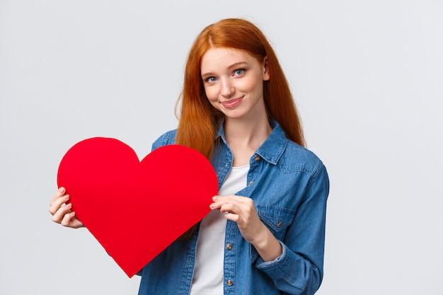 Encantadora y tímida, linda adolescente pelirroja confiesa simpatía, regala el día de san valentín, corazón rojo hecho a mano, sonríe cámara tonta y tierna, expresa amor y sentimientos, de pie blanco