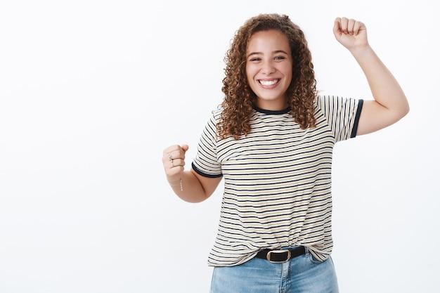 Encantadora triunfante alegre amable joven de pelo rizado cuerpo positivo chica sonriente lograr el objetivo de elevación se adapta al gesto de la victoria recibir el premio trofeo