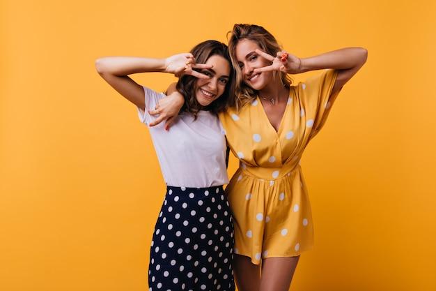 Encantadoras damas de buen humor abrazándose en amarillo. amigas con estilo posando con el signo de la paz y riendo.