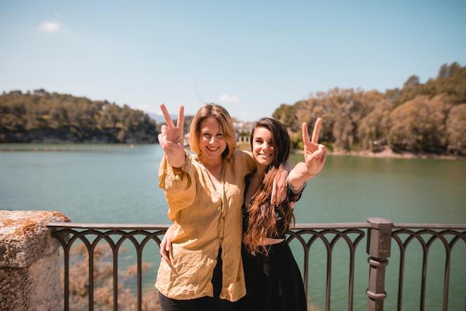 Encantadoras mujeres gesticulando la paz