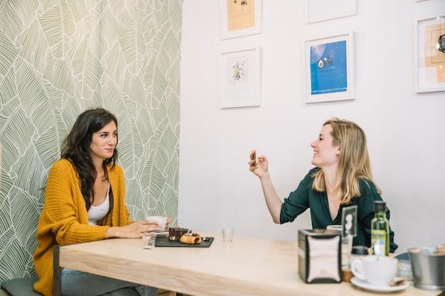 Encantadoras mujeres tomando fotos en la cafetería