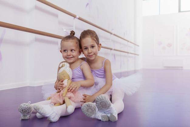 Encantadoras niñas felices con trajes de baile de ballet sonriendo a la cámara, sentados en el suelo en la escuela de ballet