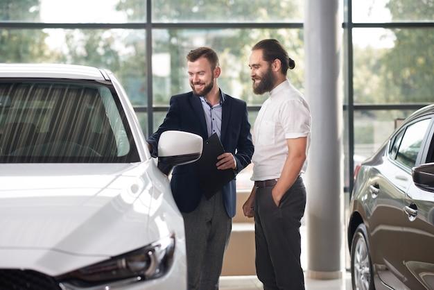 Encargado que muestra al cliente del centro de automóviles automóvil blanco.
