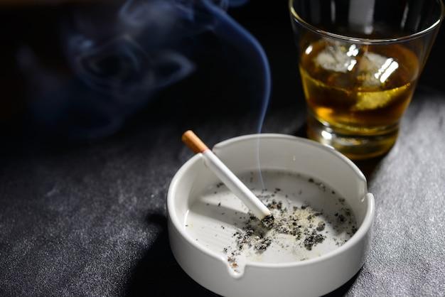 Encendido y fumar cigarrillo en cenicero con vaso de whisky