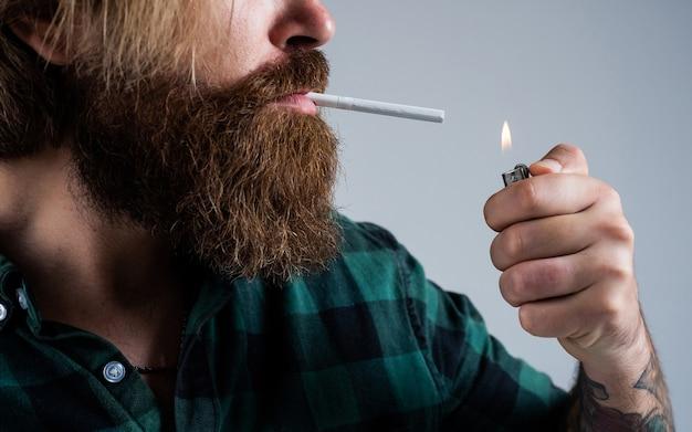 Encendiendo el cigarrillo. hombre barbudo. hábito de fumar cigarrillos. hipster brutal con bigote. modelo de moda en ropa casual. estándar de belleza masculina. luciendo tan de moda. hombre brutal seguro y guapo.