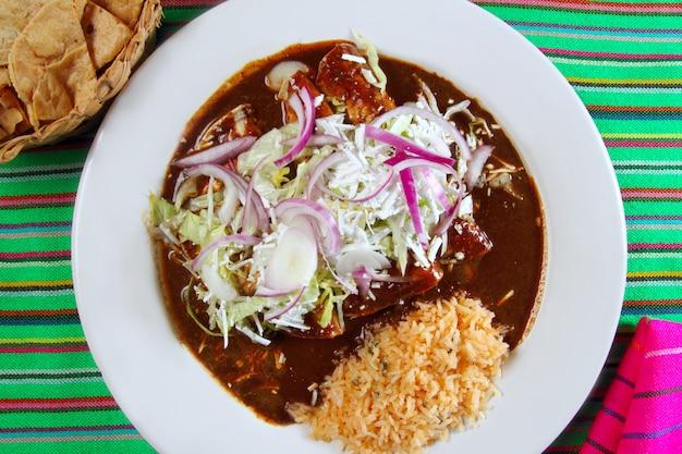 Enchiladas de mole y arroz de la comida mexicana.