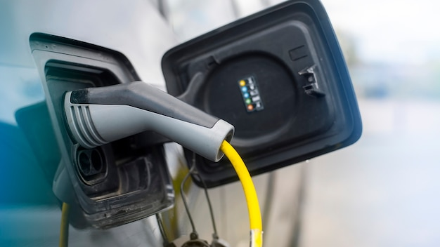 Enchufado el cargador a un coche eléctrico en la estación de carga
