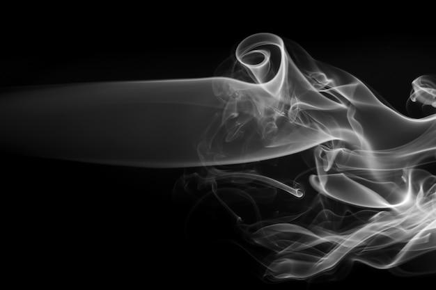 Encienda el extracto del humo blanco de fo en fondo negro. concepto de drakness