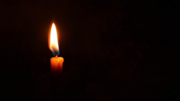 Encienda la luz de la vela aislada en fondo negro