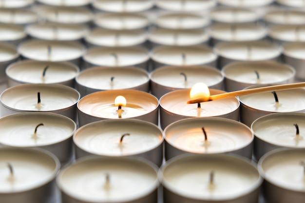 Enciende muchas pequeñas velas redondas, de cerca.