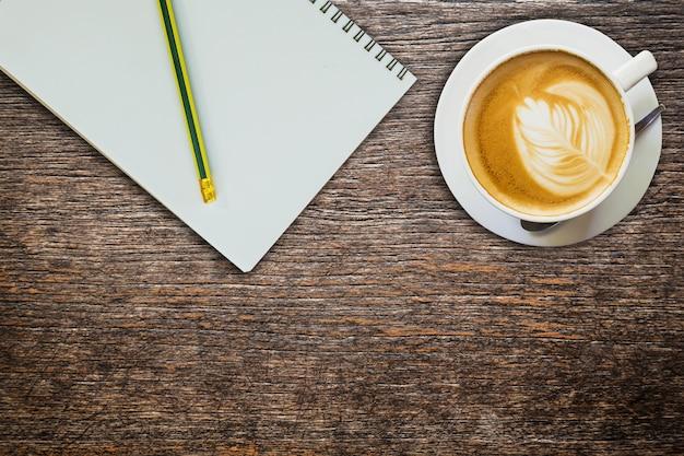 Encima de café y cuaderno con lápiz sobre textura de madera