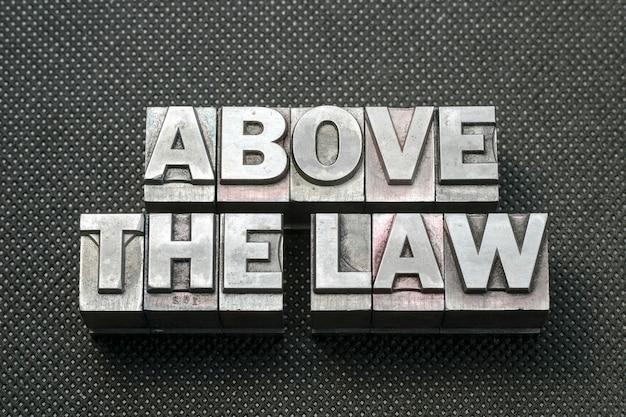 Por encima de la frase de la ley hecha de bloques de tipografía metálicos sobre superficie perforada negra