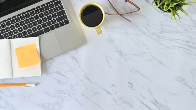 Encima de la mesa de tiro, mesa de mármol de escritorio de oficina con computadora portátil, papel de cuaderno, lápiz, vasos y taza de café.