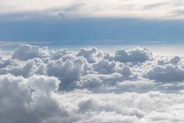 Por encima de las nubes esponjosas con cielo azul de avión