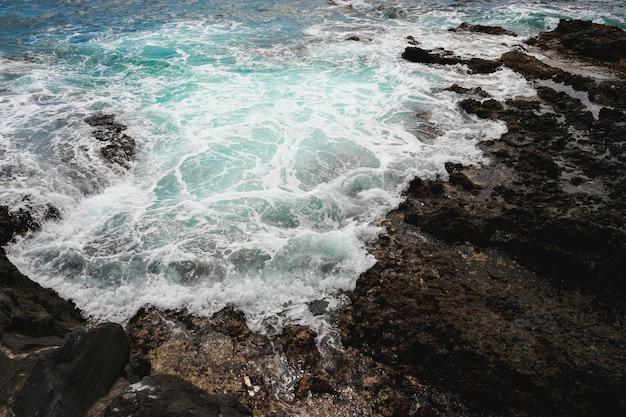 Por encima de las olas de vista en la costa rocosa