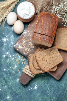 Por encima de los trigos pan negros dietéticos en la tabla de madera espigas flor huevos harina en un tazón sobre fondo azul.