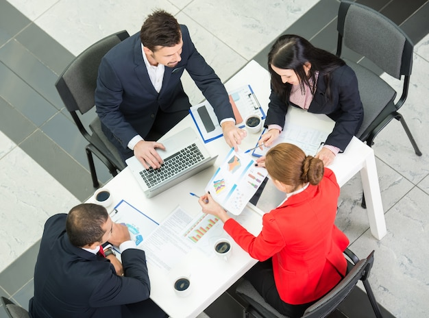 Por encima de la vista del equipo de negocios están sentados alrededor de la mesa.