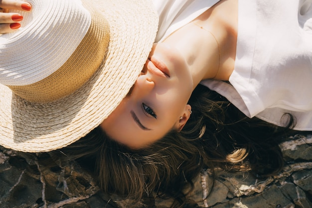 Por encima de la vista de una mujer encantadora en blusa blanca y sombrero de paja. retrato de niña de maquillaje natural con el pelo largo en la playa de roca. kit de maquillaje, ambiente veraniego, concepto de piel pura