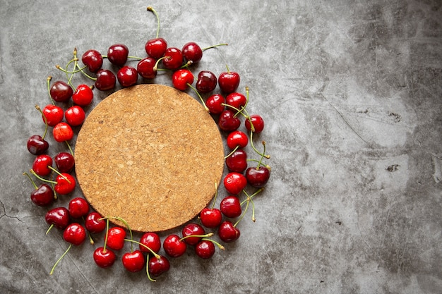 Encimera de mármol, soporte de corcho para caliente, y cerezas. temporada de verano, cosecha de bayas, mermelada, compotas, lugar para inscripciones