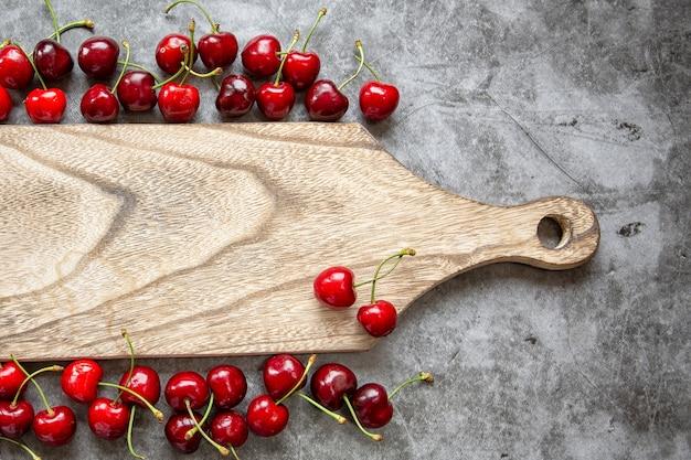 Encimera de mármol, tabla de cortar y cerezas. temporada de verano, cosecha de bayas, mermelada, compotas