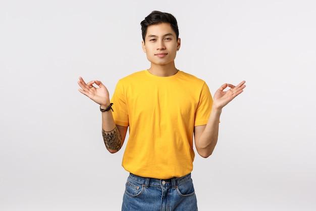 Encuentra la paz dentro de tu alma. tranquilo y aliviado, pacífico joven guapo tatuado chico asiático meditando, liberar el estrés, extender las manos de lado con orbes zen, alcanzar el nirvana, sentir paciencia