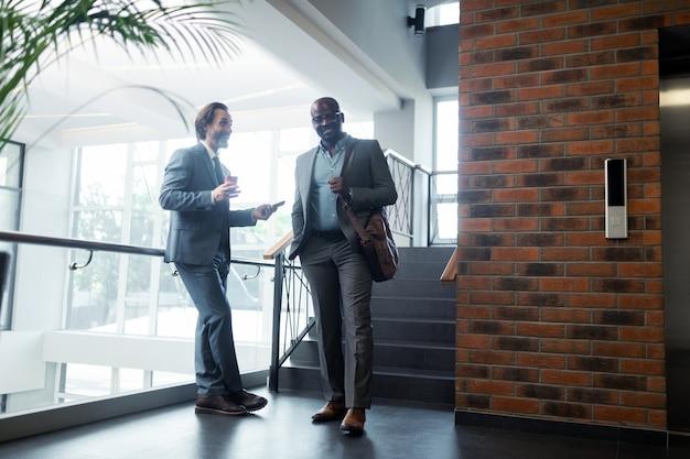 Encuentro cerca del ascensor. dos hombres de negocios vestidos con trajes sonriendo mientras se reúnen cerca del ascensor