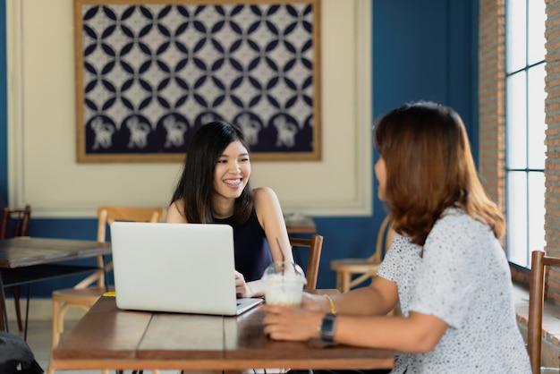 Encuentro freelance de chicas asiáticas con un colega en la cafetería.