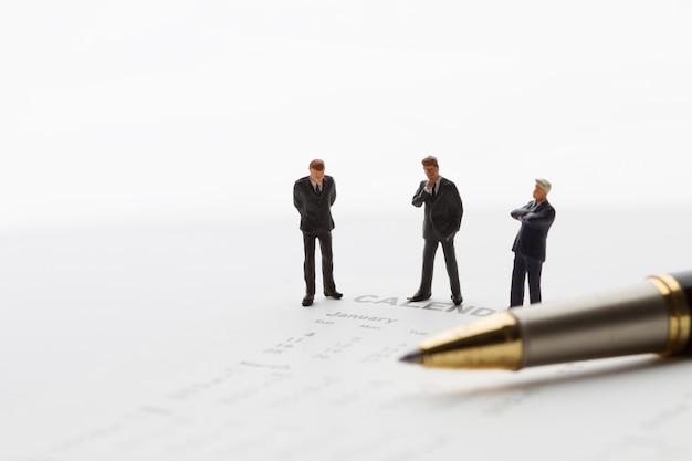 Encuentro de hombre de negocios en miniatura con calendario