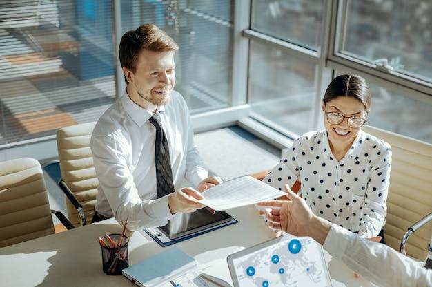 Encuesta importante. joven alegre y agradable entregando un cuestionario a su colega, pidiéndole que lo llene, mientras participa en la reunión.