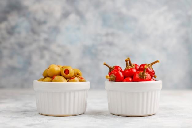 Encurtidos pequeños redondos red hot cherry chili peppers sobre hormigón gris