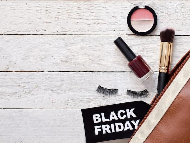 Endecha plana con accesorios cosméticos y bolsa con cartel de viernes negro en madera blanca, copyspace